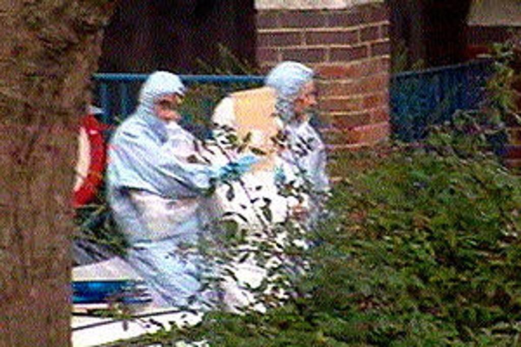 En av de mistenkte føres bort fra leiligheten i Notting Hill.