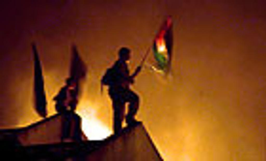 Palestinere flagger på toppen av en brennende synagoge i den tidligere jødiske bosetningen Netzarim nord på Gazastripen mandag.