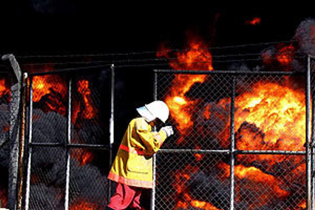 En irakisk brannmann forsøker å åpne en port ved brennende oljeledninger nord i Irak 24. oktober 2005, etter at opprørere gikk til angrep på ledningene.