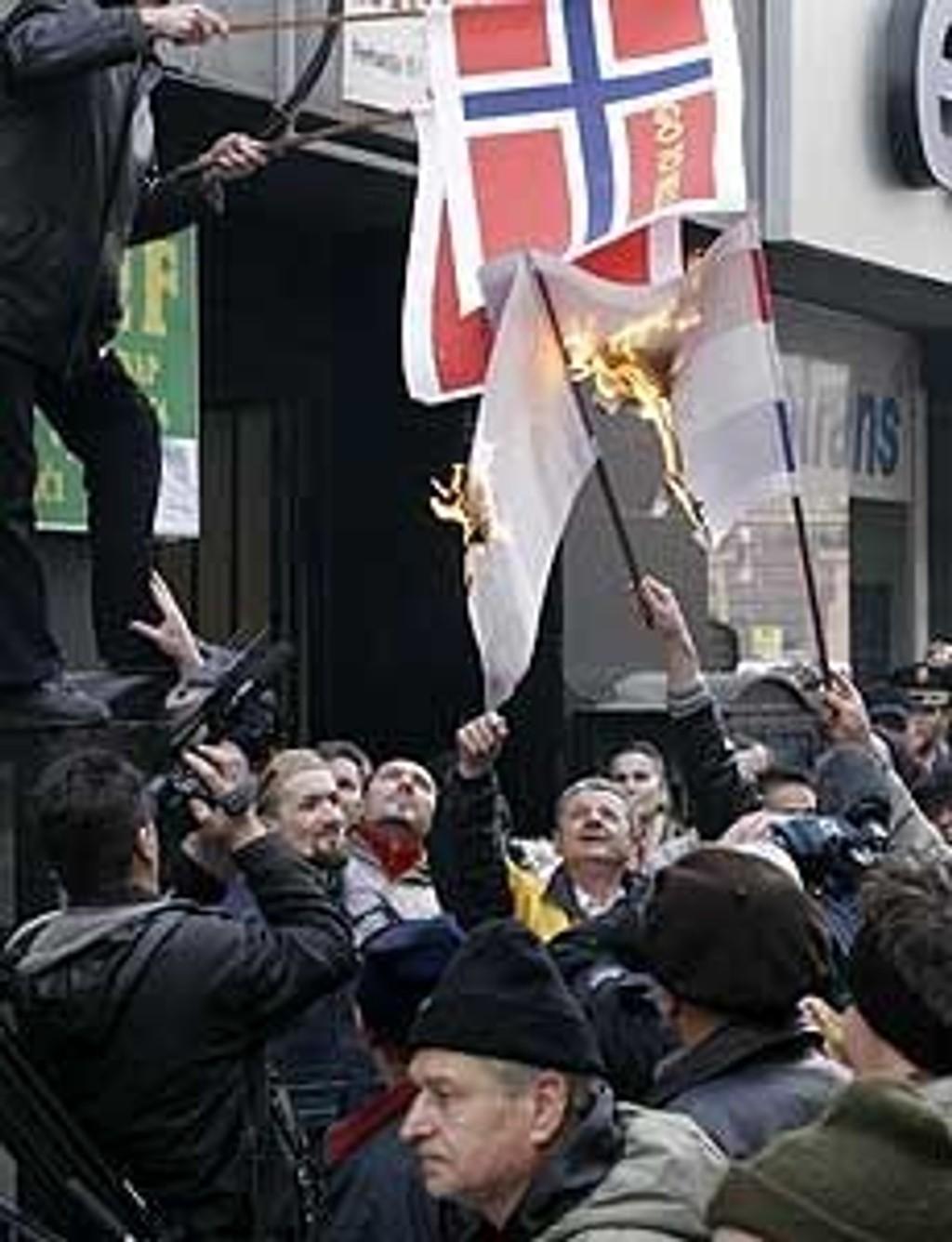 Demonstranter brenner norske og danske flagg utenfor den norske ambassaden i Sarajevo onsdag.