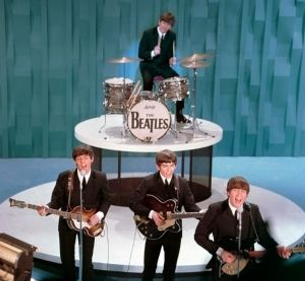"The Beatles perform on the ""Ed Sullivan Show"" in New York in this Feb. 9, 1964, file photo. From front left are, Paul McCartney, George Harrison and John Lennon. Ringo Starr is on drums."