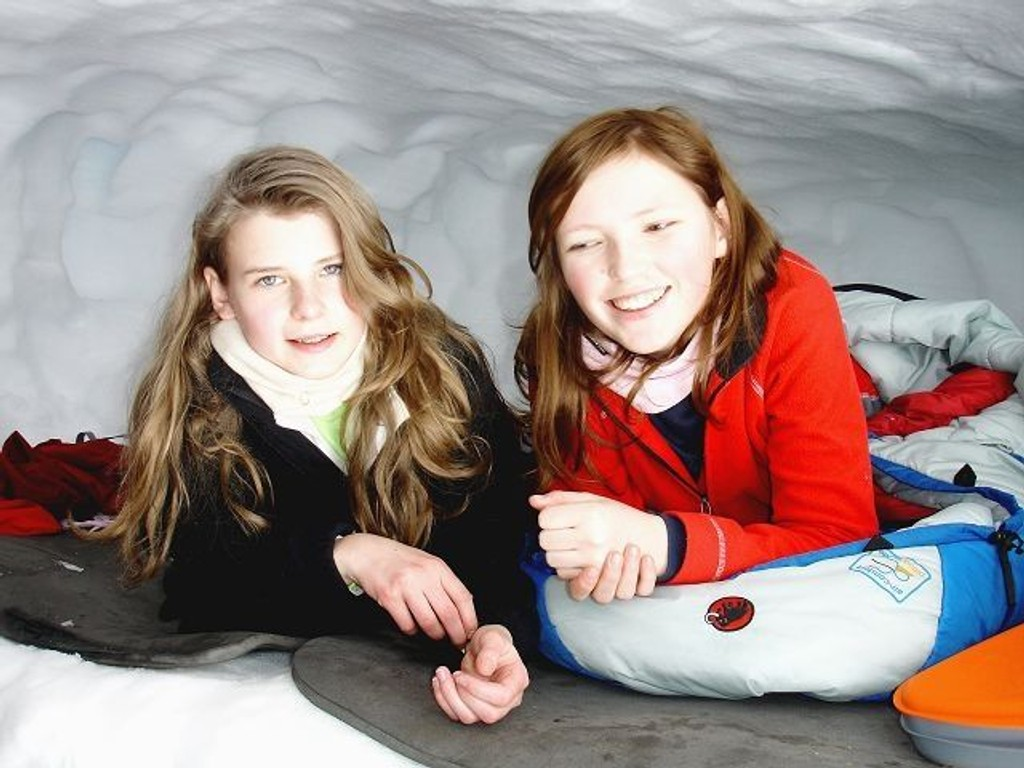 Rikke Riisnæs (13) og Nora Øien Spilsberg (14) smiler godt etter en komfortabel natt i snøhula.