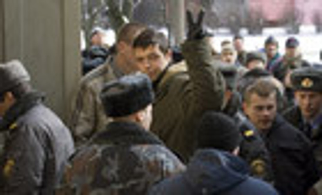 Detained opposition activist flashes the victory sign as he passes a police cordon and enters a court building in Minsk