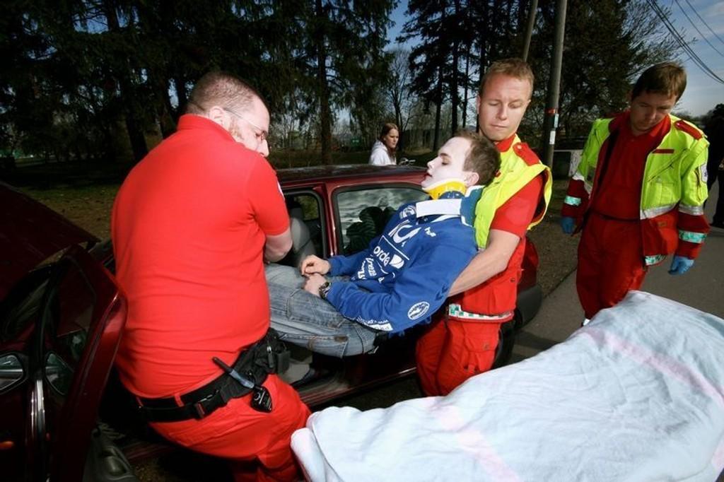Sondre Nygard blir løftet fra bilen og over på båren av ambulansepersonell som er under opplæring.