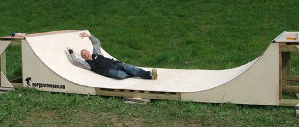 Vaktmester Øyvind på Jeriko skole tester ut skateboardrampa etter å ha hjulpet til med monteringen.