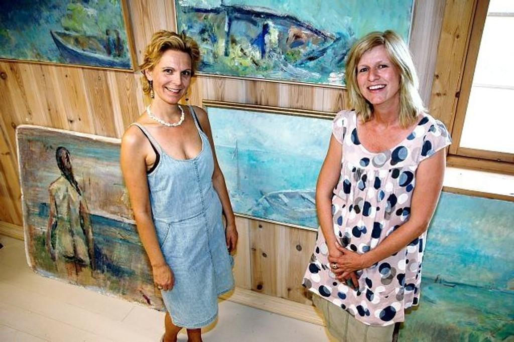 Merete Arnevåg og Tone Welhaven Føyen foran et knippe av Grethe Scheis sommerlige malerier.