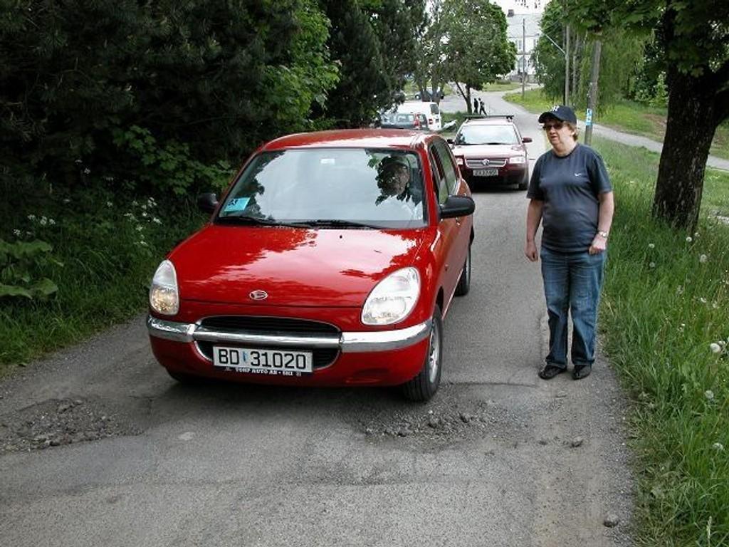Reidar Stormo «lirker» bilen frem for å unngå hullene på veien til Lambertseter gård. Samtidig må han passe på at han ikke presser fotgjenger Gerd Mikkelsen ut i grøften.