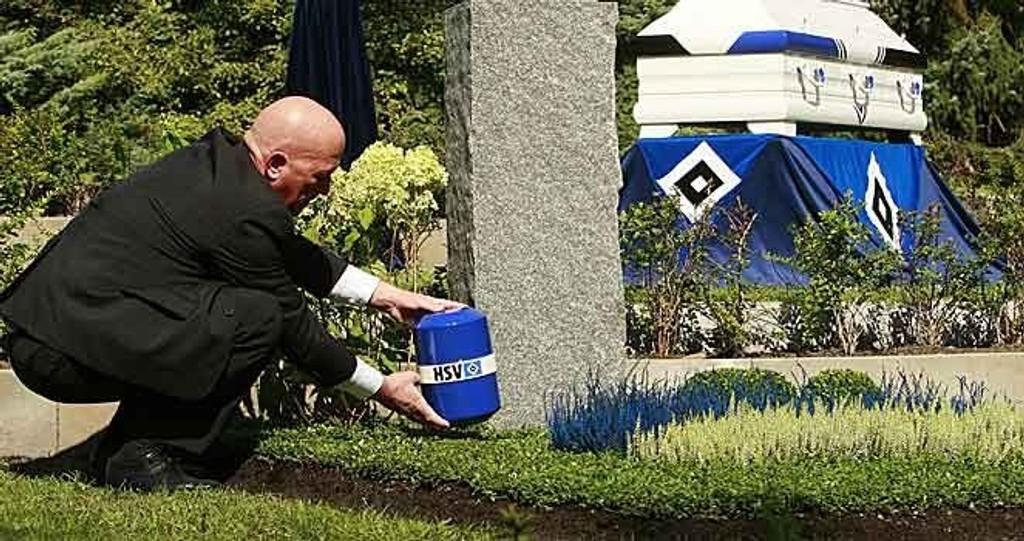 Holger Langer plasserer en urne med Hamburger SportsVereins emblem i en grav på Altona kirksgårde for fotballfans.