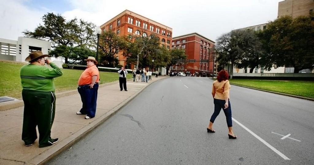 Millioner har søkt til Dealey Plaza etter snikmordet på John F. Kennedy. Her fyrer Hazen Smith (til venstre) fra Long Island løs mens sønnen Julian breier seg ved Elm Street.
