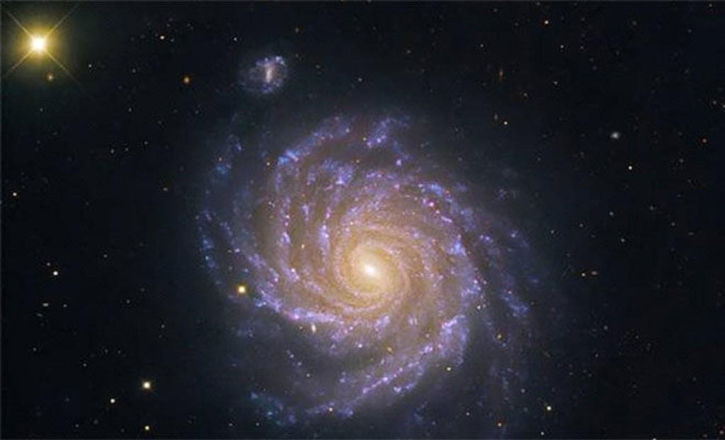 SPIRALGALAKSE: Dette er et bilde av NGC 1232, en spiralgalakse som blir sett rett på. Lysflekken oppe til venstre er en liten satelittgalakse (NGC 1232 A).