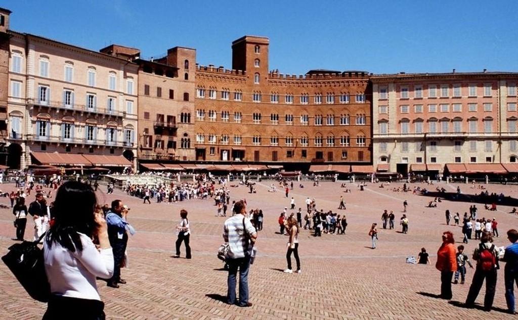 Italienere og turister samles på Piazza del Campo i Siena.
