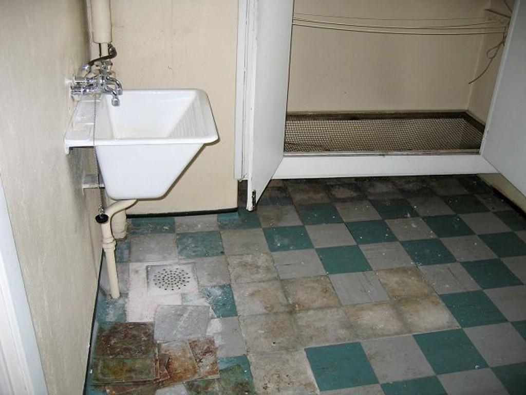 Vaskerommet har en utslagsvask, men ingen vaskemaskiner. Tørkesnorene er brune, og rommet er tydelig preget av manglende vedlikehold.