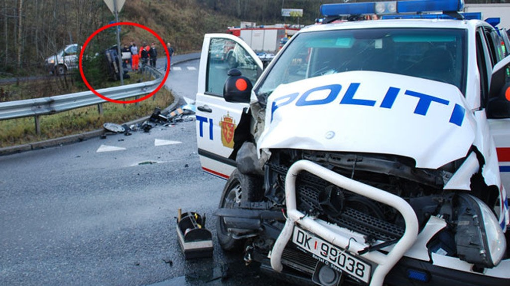 DOBBELULYKKE: Bak ser du bilen som havnet på siden. Politibilen krasjet med en tredje bil i samme krysset.