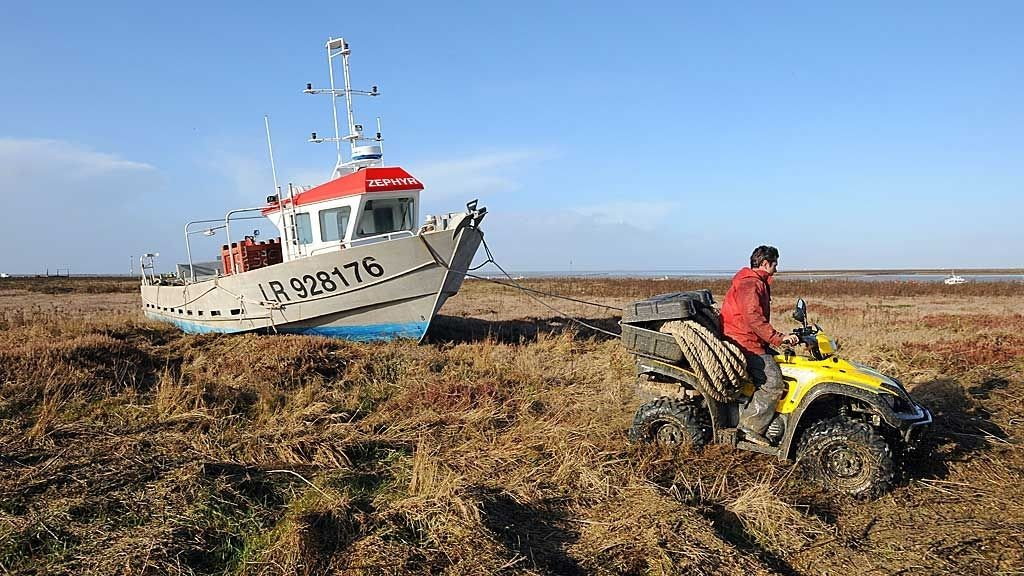 An oyster fishing boat is pulled by a tractor in a field of Port du Pave, near Charron western France, on February 10, 2009. Hurricane force winds lashed France Today, knocking out power to hundreds of thousands of households and prompting the closure of Paris' two international airports for the first time in 34 years. Some 300,000 households in western France were without power this morning, the electricity grid operator ERDF said.