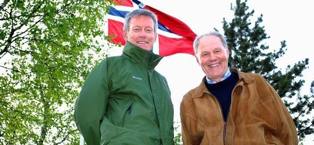 Arne Mathisen (t.h) og Per Skau, to av de 17 medlemmene i Mærradalen mannskor international, her ved flaggstangen som de har stått ved hver eneste 17. mai siden 1979! Foto: Fredrik Eckhoff