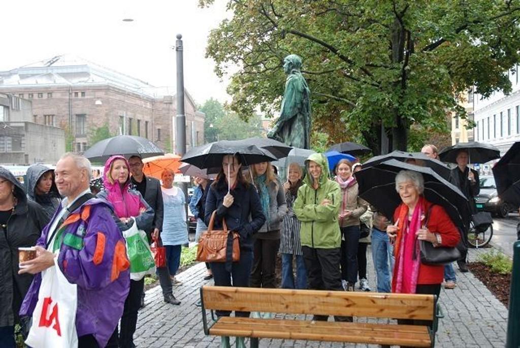 Et knippe paraplybekledte mennesker.