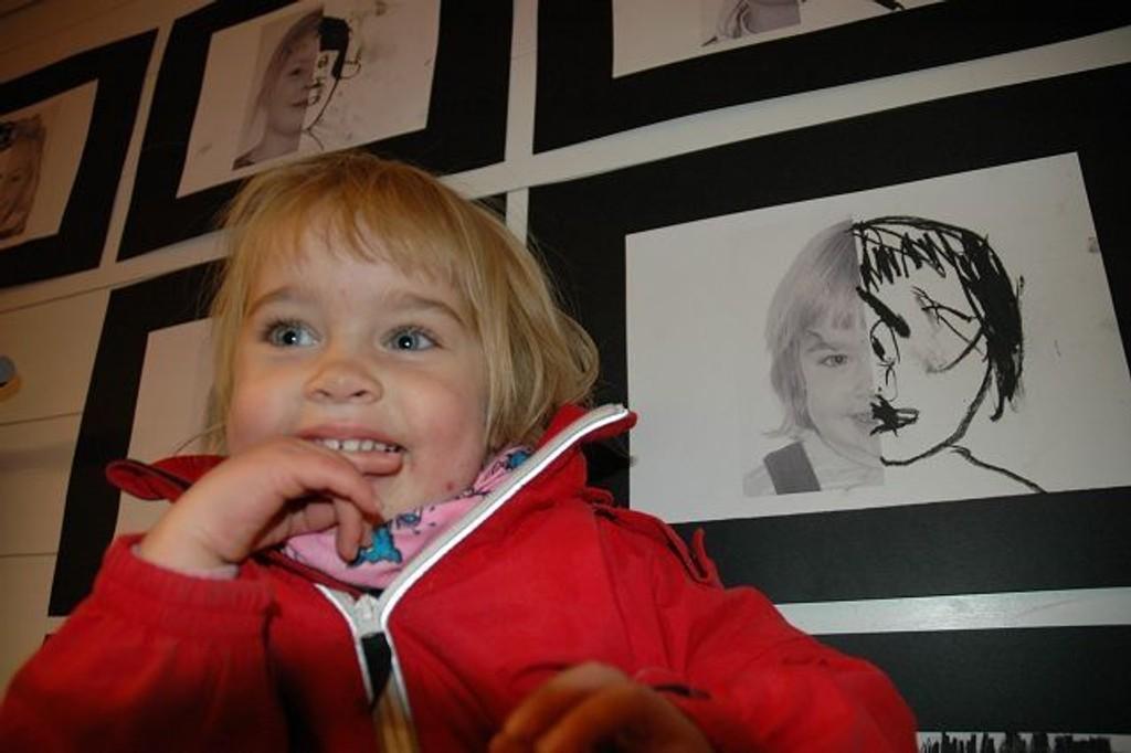 Ane Solberg (2) syntes det var kjempegøy å vise frem kunstverkene sine til mamma og pappa. Her foran et selvportrett i form av både fotografi og kullstift. Foto: Nina Schyberg Olsen