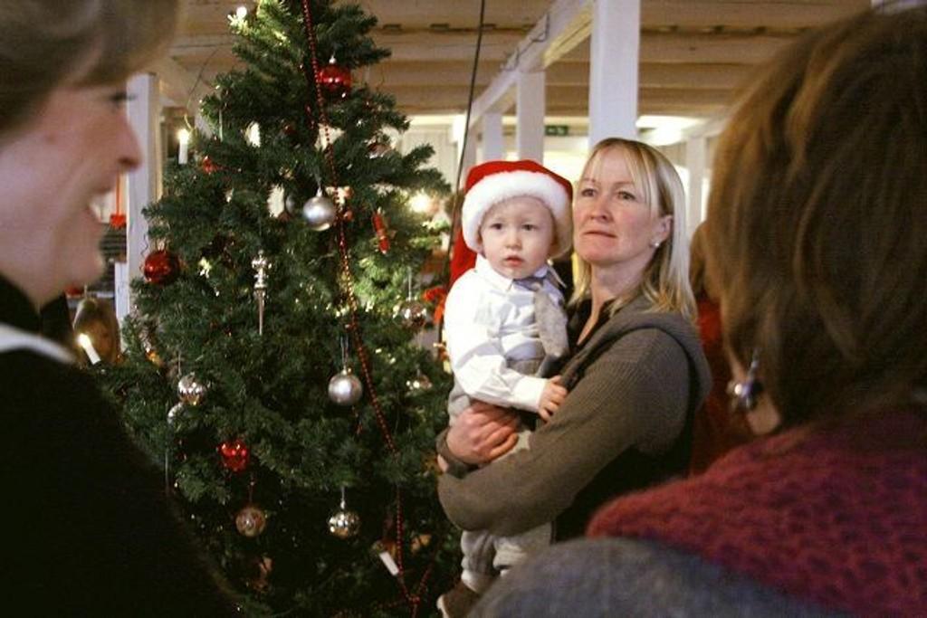 Ivan V. Simensen sitter trygt på bestemor Astrid Hagens arm mens de går rundt juletreet på Årvoll gård.
