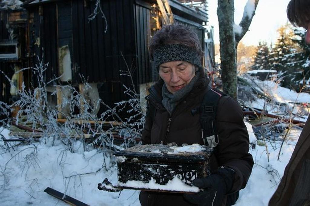 Bjørg Christiansen med sitt smykkeskrin foran den utbrente leiligheten i Brattvollveien. FOTO: Anne-Grethe Ulriksen