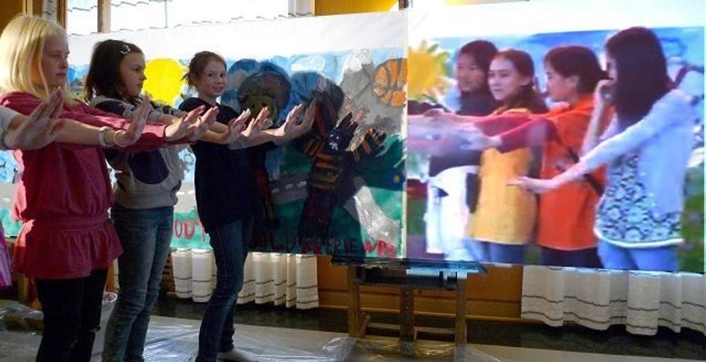 (F.v.) Julie Maria Jensen Storvik, Linnea Kjelstrup og Henriette Byermoen rekker hender til elever i Korea. Den norske delegasjonen til venstre i bildet, koreanske kunststudenter direkte fra verdenskonferansen til høyre.