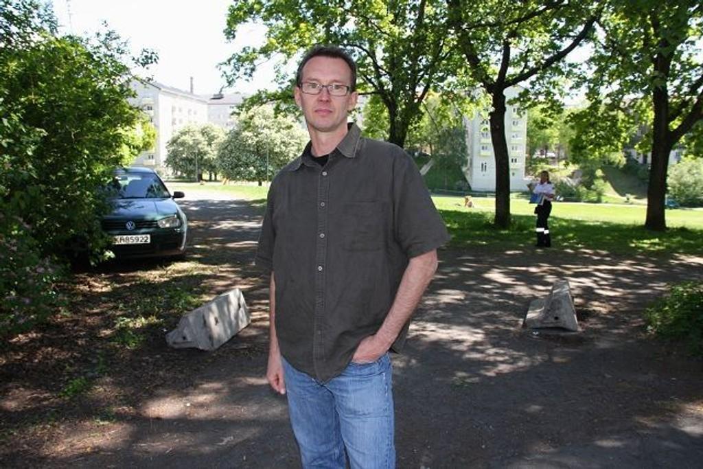 Parkforvalter Magnus Nilsson i Bydel Sagene synes det er trist å måtte sette opp nye sperringer rundt Iladalen park. I bakgrunnen tar Trafikketaten bilder av kjøretøyet. FOTO: LARS ROAR RUD
