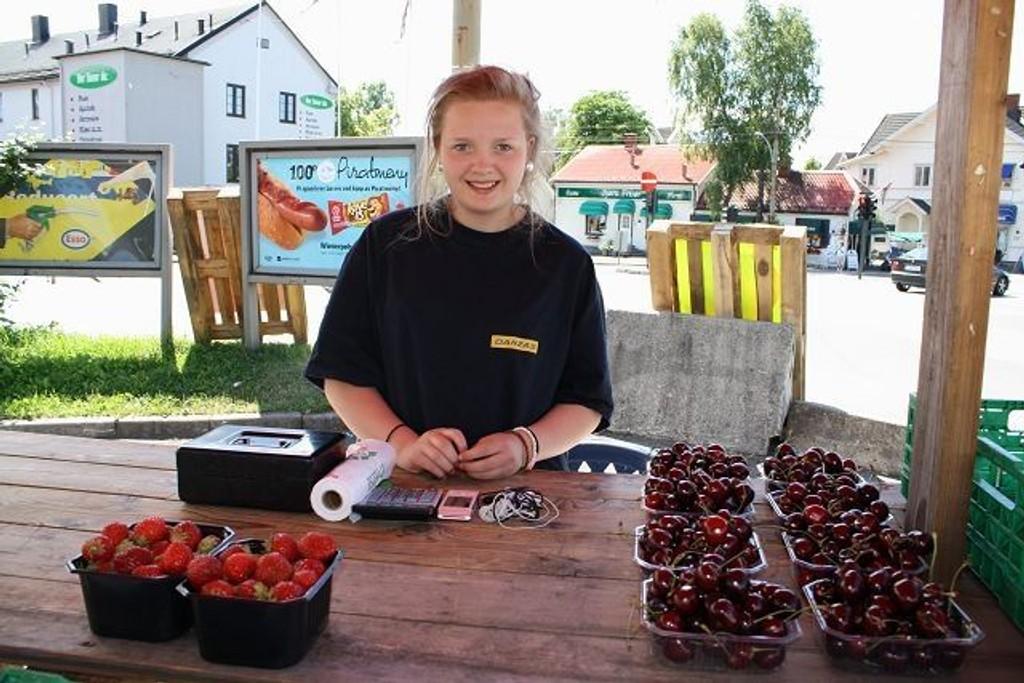Bærsultne kunder: Helene Thorvaldsen (14) har solgt mange bærkurver i dag. Salgsboden i Sæter-krysset har vært populær i varmen. Foto: Helene Falstad