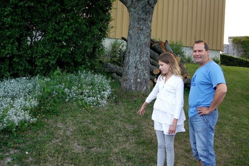 Sandra og Erik Bredesen hører stadig vekk at de har besøk i hekken. Her viser datteren hvor snylteren pleier å sitte. Foto: Helene Falstad