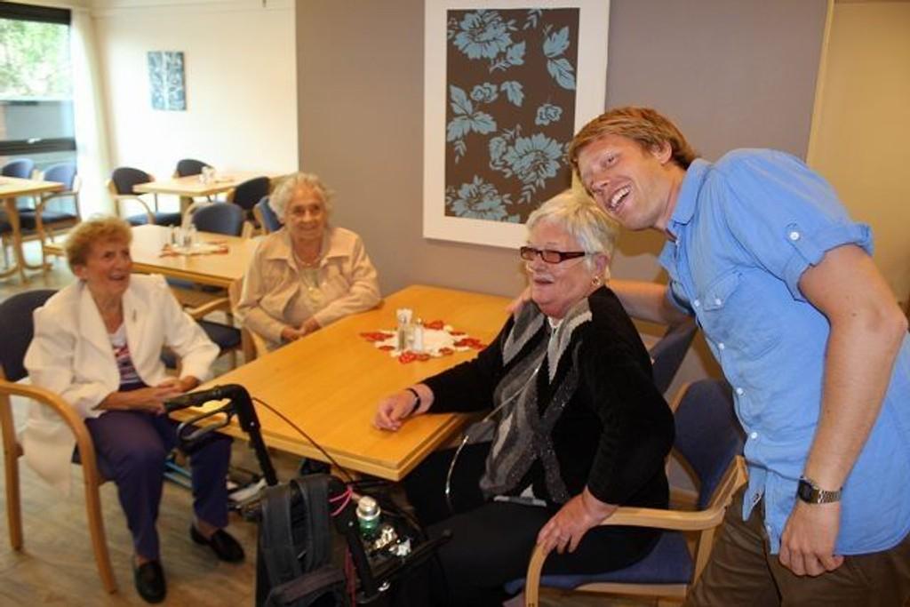 Knut Erik Aas (26) har alt rukket å sjarmere damene på seniorsenteret i senk. Fra venstre Aslaug Stensrud, Anna Engh og Britt Nordhagen. – Han er jo en så kjekk kar, skryter damene.