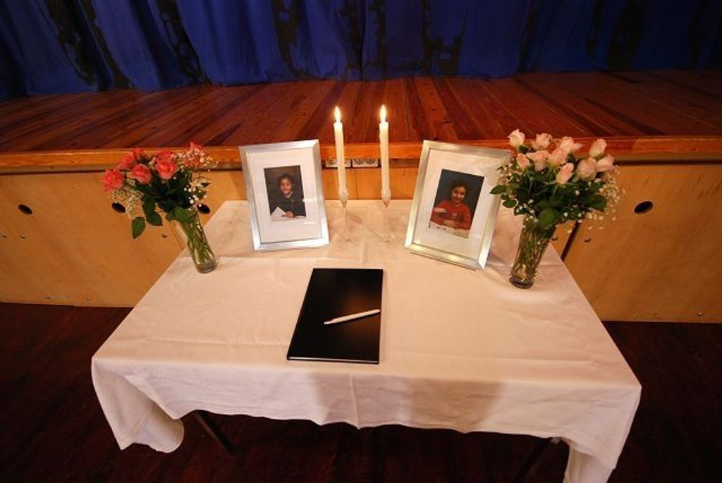 To lys brenner ved siden av bilder av de to jentene Narim (9) og Nesrin (7) under minnestunden på Stenbråten skole fredag morgen.