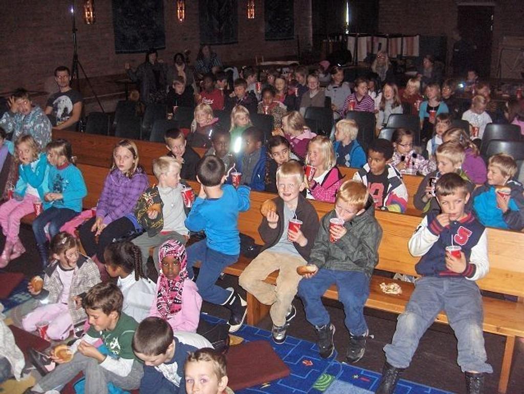 Her, i menighetssalen i Lambertseter kirke, sitter rundt 100 barn fra Akitivitetsskolen på Lambertseter skole og koser med saft og boller mens de ser Toystory-film i høstferien.