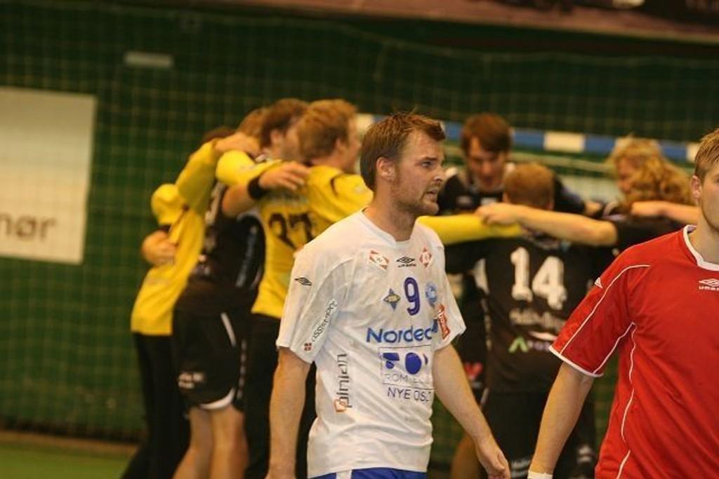 Spillende trener, Michael Bech Rehnqvist, tusler av banen mens Elverums spillere jubler for semifinaleplassen i bakgrunnen.
