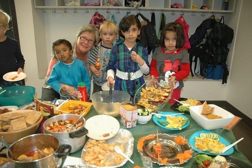 Barne- og ungdomsarbeider Trine Kasa foran matbordet i Bakkehavn barnehage, her sammen med Felix (f.v.), Harald og søstrene Rihab og Hibah.