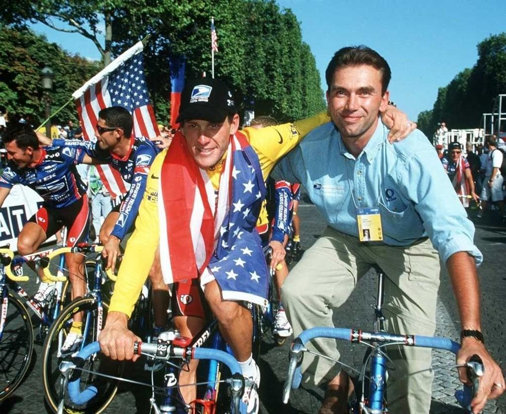 1999: Lance Armstrong og Johan Bruyneel feirer den første sammenlagtseieren i Tour de France. Armstrong syklet da for US Postal, og man ser lagkameratene hans juble i bakgrunnen.