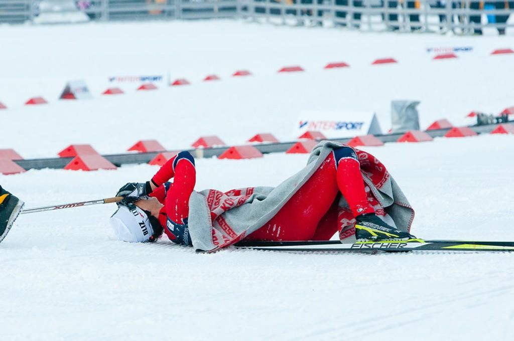 Marit Bjørgen ligger i målområdet etter sitt gulløp på 10-kilometeren, fullstendig utmattet.