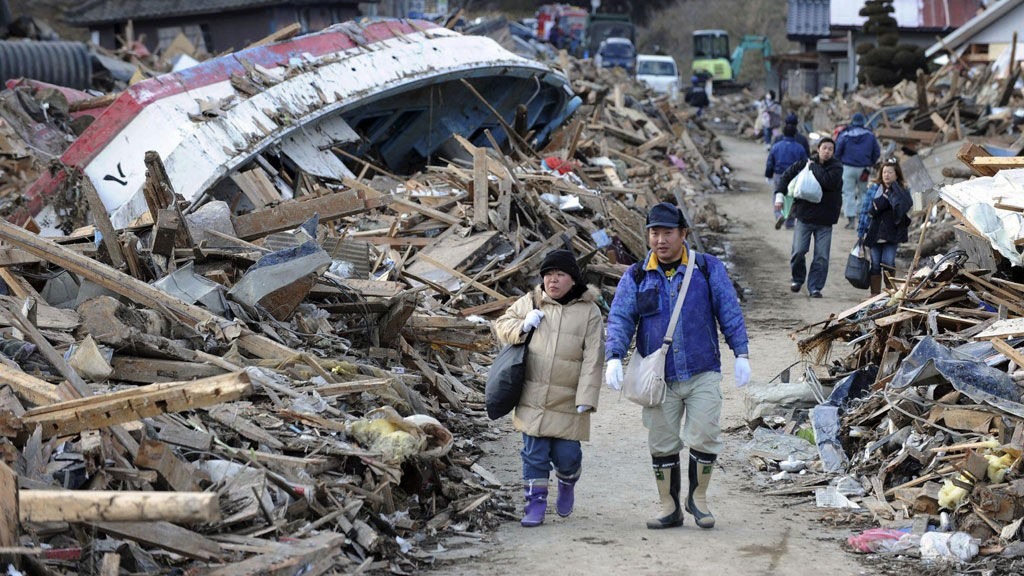 To personer går blant de store ødeleggelsene i Minamisanriku.