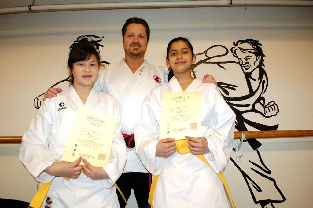 Desiree Berg(t.v) og Juhi Saigal viser stolt frem diplomen de fikk av Norges høyest dekorerte i kampsporten Hapkido, Henrik Hunstad.