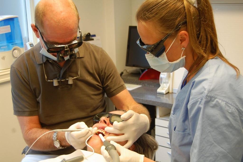 Ellen Marie Haugen merker ikke laseren som pulserer på det betente tannkjøttet hennes. Tannlegeassistent Nina Anstensen bistår Einar Bjart Haugen med behandlingen.