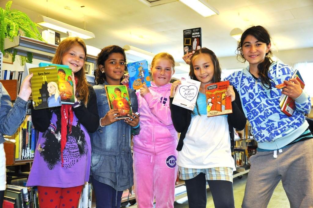 Jentene på femte trinn ved Grorud skole viser gladelig frem litteraturen de har valgt.