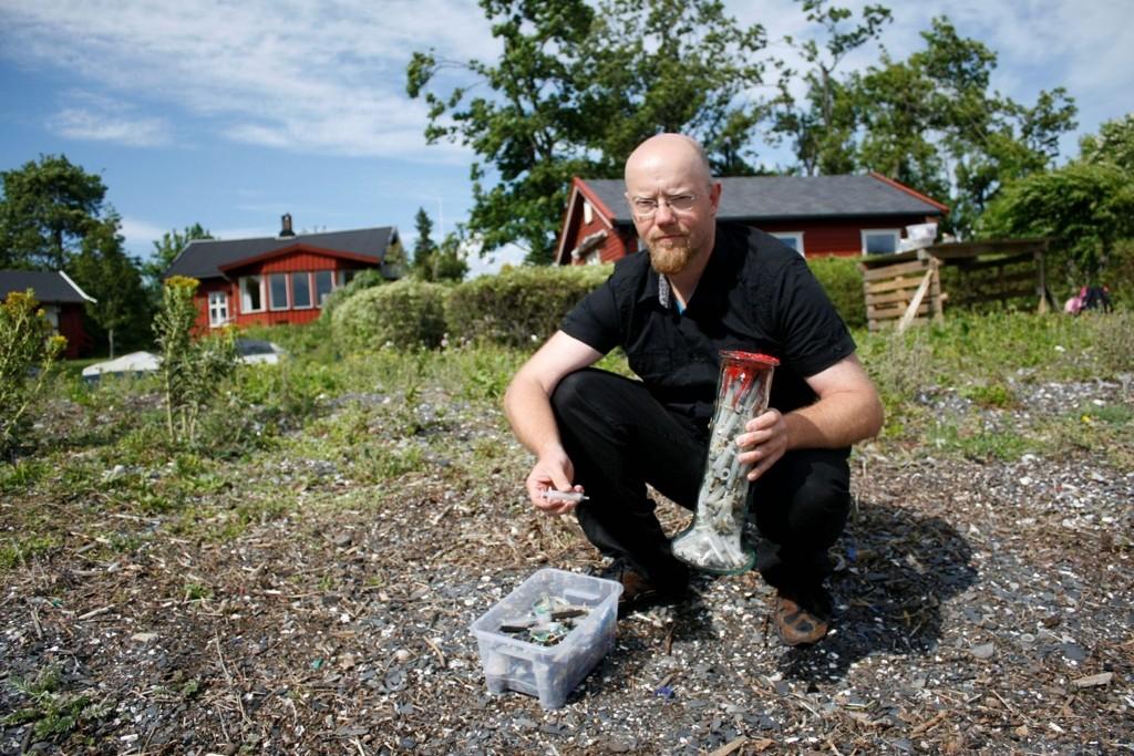 SPRØYTER: Johan van den Boom lager kunst av søppel fra sjøen, blant annet har han fylt en stor vase med sprøyter. Mange av sprøytene og mye søppelet Boom plukker kommer på strendene er blitt skyllet ut i sjøen fra kloakken.