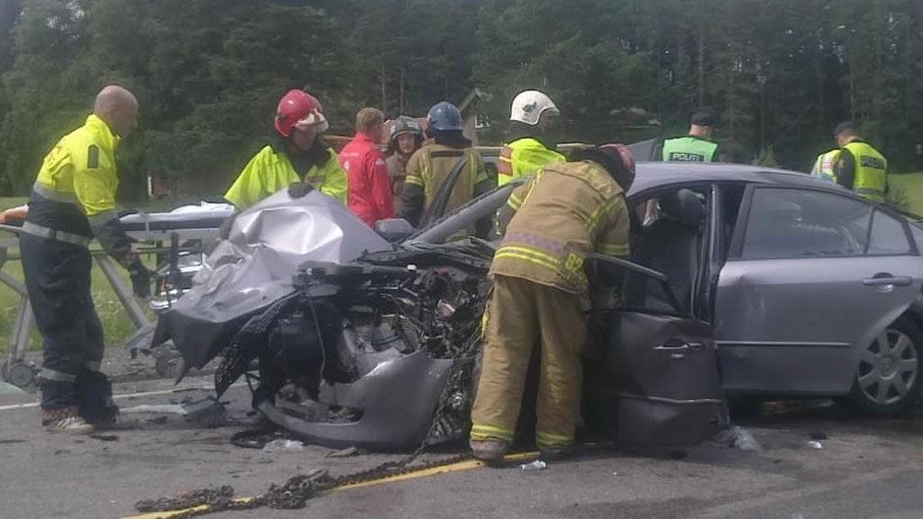 Brannvesen og ambulanse-personell jobber for å få den hardt skadde personen ut av bilvraket.