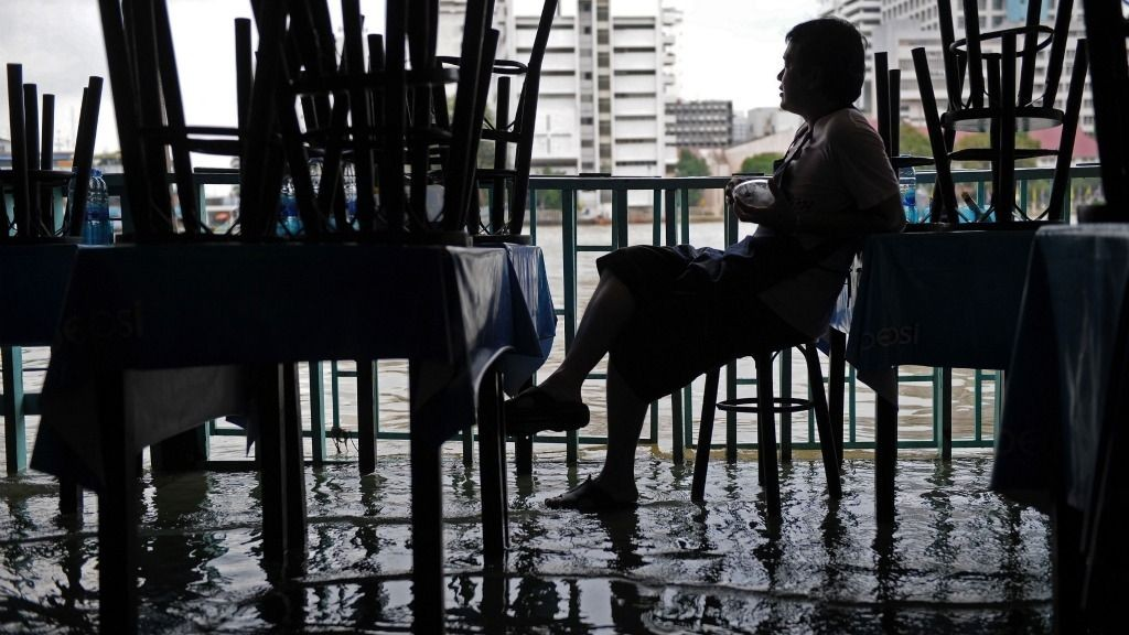 A Thai employee of a riverside restaurant sits idle on a stool as water from the Chao Phraya river floods low-lying areas of downtown Bangkok on October 4, 2011. Thailand's worst monsoon floods in decades have killed 224 people and affected three quarters of the country, including part of the ancient city of Ayutthaya, officials said.