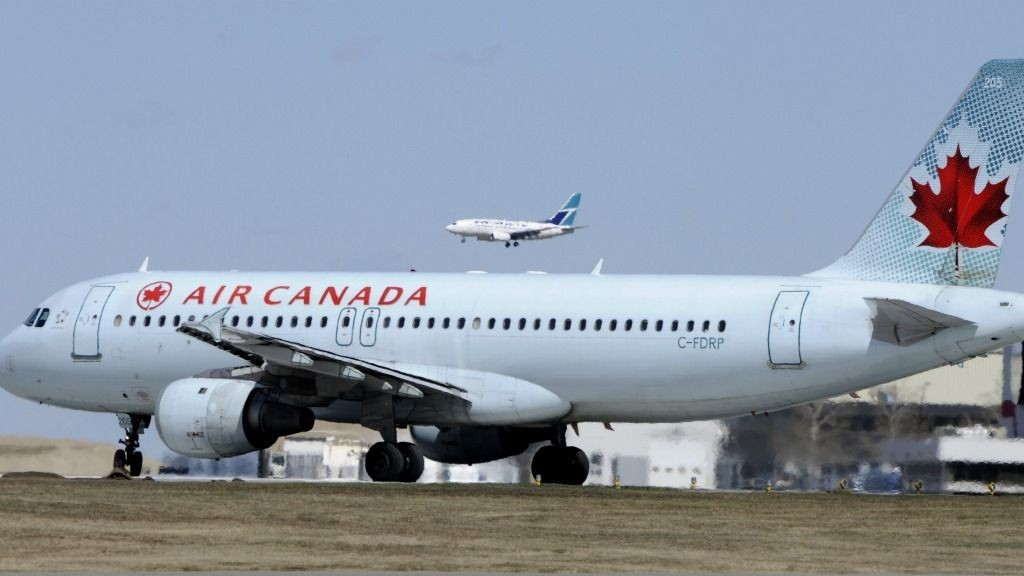 An Air Canada Airbus A320 prepares to take off as a Westjet Airlines Boeing 737 jet lands in the background lands at Calgary, Alberta.