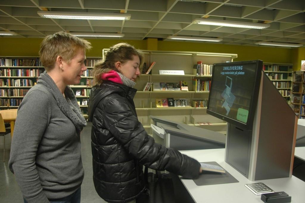 MODERNE: Marie Tørnes liker moderniseringen av Oppsal bibliotek, og nølte ikke med å ta i bruk den nye låneautomaten. Her sammen med avdelingsleder Heidi Stene, som lover at alle skal få hjelp til å lære seg det nye systemet.