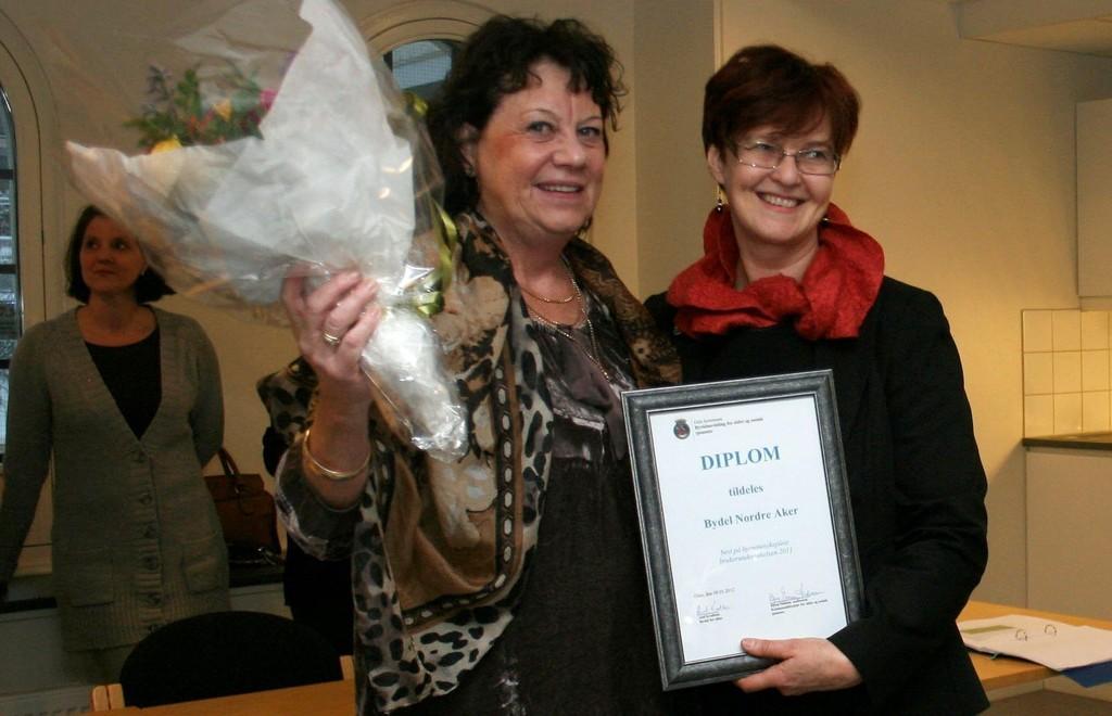 BLOMST OG DIPLOM: Eldrebyråd Aud Kvalbein (KrF) delte ut diplom og blomster til Bydelsdirektør Mona Taasen for bydelens gode resultater i brukerundersøkelsen for 2011. Spesielt fornøyde er brukernemed møtene med pleierne.