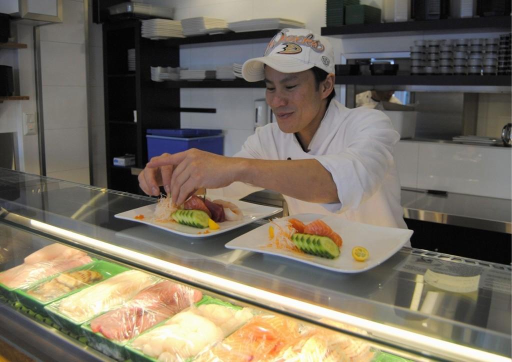 Kokken, Ho, Si Tuan, har utdannelse fra sushi-akademiet i L.A. Her legger han opp sashimi med agurk og annet tilbehør.