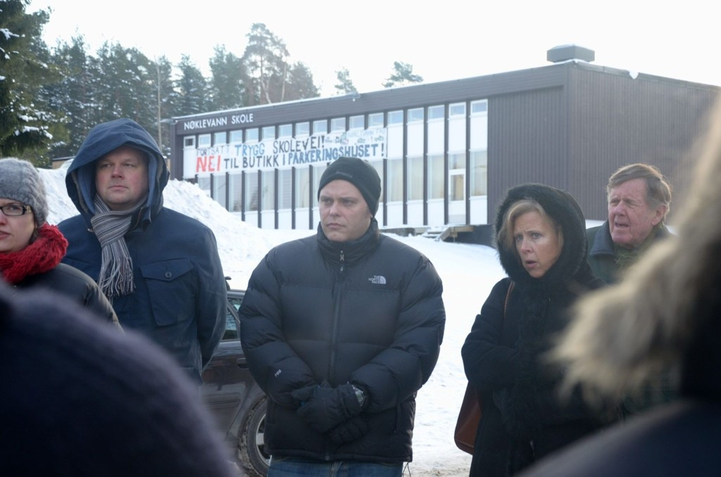 ENGASJERT: Leder av bystyrets byutviklingskomité, Jøran Kallmyr (i midten), ledet befaringen av garasjeanlegget i Bølerlia 73. Banneret på nærmeste nabo, Nøklevann skole, etterlot ingen tvil om hva nærmiljøet mener om saken.