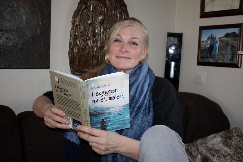 Med fars maleri: Gro Inglingstad hjemme i sofaen på Holtet med debutromanen, «I skyggen av et maleri». Omslaget, malt av hennes far, gir henne noe av den fortaptheten personene i romanen hennes opplever.