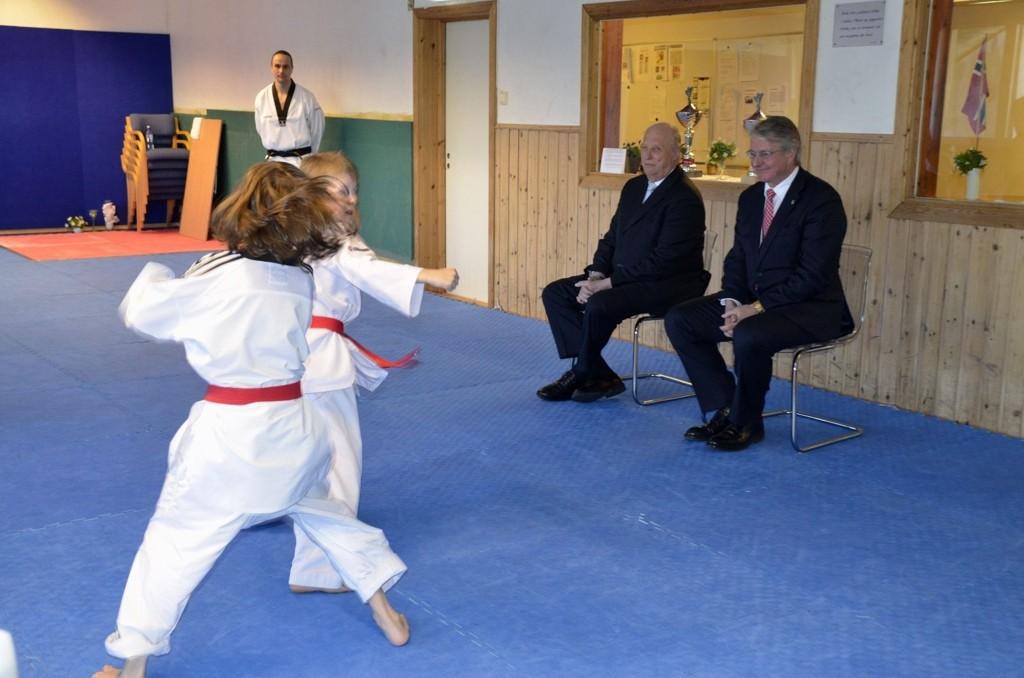 OPPVISNING: Mikael Oguz står i bakgrunnen og ser på sine to taekwondostudenter opptre foran kong Harald og ordfører Fabian Stang.