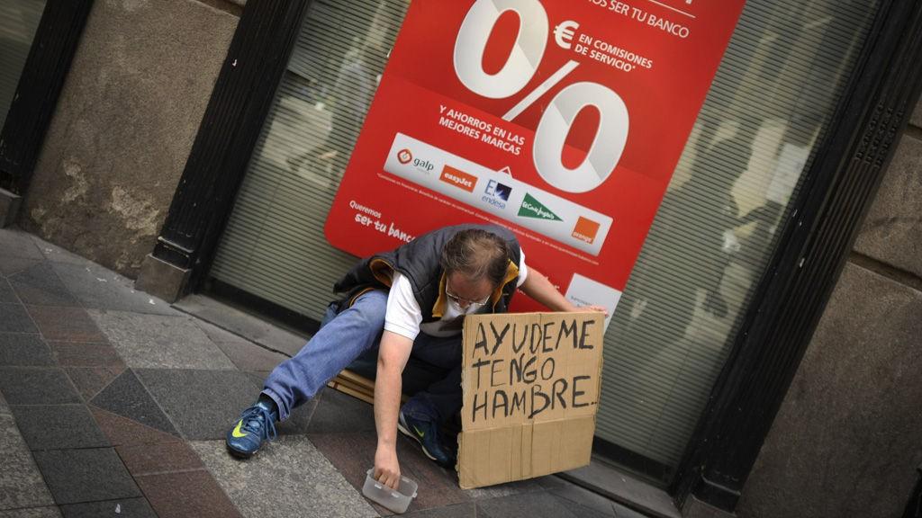 En mann sitter foran en bank i Madrid 9. juni med skiltet «Hjelp meg, jeg er sulten». Spania trenger 100 milliarder Euro for å sikre bankene sine og unngå økonomisk kollaps.