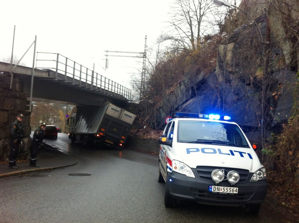 LITT FOR HØY: Den danske lastebilen har fått knust kapellet og har det ene bakhjulet i lufta etter sammenstøtet med broa i Nordstrandveien.